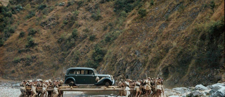 Porteadores transportan automóvil a través de un arroyo en Nepal, 1948. Fotografía de Volkmar Wentzel.